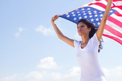 best ways to bring spouse to US wife holding USA flag in her hands